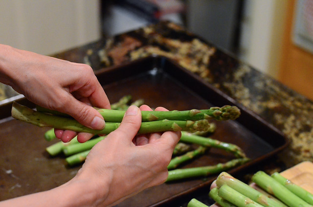 Asparagus being trimmed by hand breaking them.
