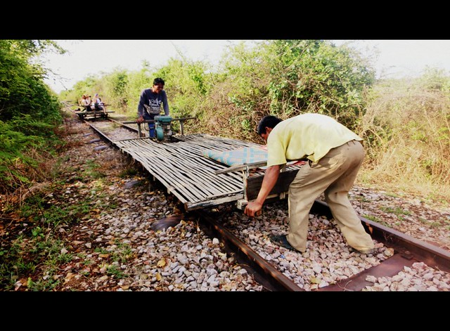 Lifting the bamboo train off the tracks so others can pass