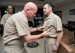 Outgoing Fleet Master Chief John Minyard, left, pins the Fleet Master Chief insignia onto oncoming Fleet Master Chief Marco Ramirez as Adm. Cecil D. Haney, commander of U.S. Pacific Fleet, presides over the small ceremony. (U.S. Navy photo by Mass Communication Specialist 1st Class Amanda Dunford)