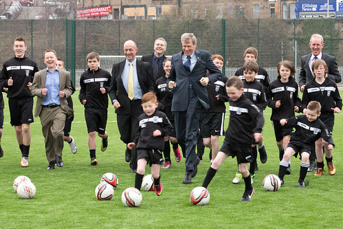 Men in suits play football with Leith Athletic members at Meadowbank