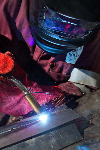Close up of a person wearing a welding mask and welding a piece of metal
