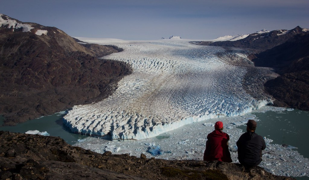 The Glaciar O'Higgins calving from the Southern Patagonian Ice Cap into the southwestern arm of the Lago O'Higgins. The glacier front sticks out 60m above the water surface. It takes 2 days from Candelario Mancilla to get to this remote rocky outcrop towering high above the ice. Aysen. Patagonia. Chile.