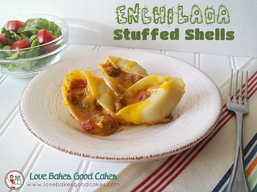 Enchilada Stuffed Shells on plate with fork, and green salad with tomatoes.