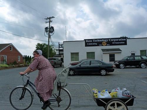 Mujer amish en bicicleta llevando la compra