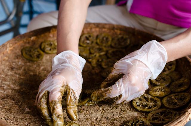 人力將檸檬片鋪滿竹篩