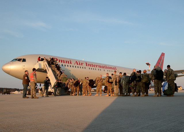 Airmen load into a plane headed for their deployment