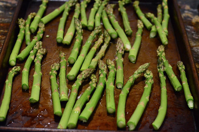 Asparagus arranged on a baking sheet.