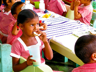 Eating a Healthy Snack: A little girl eats a peanut butter sandwich with classmates