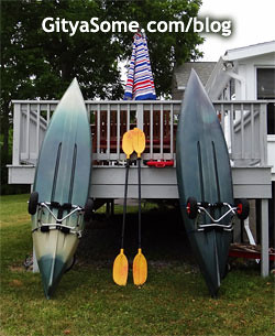 Two kayaks on wheels standing up