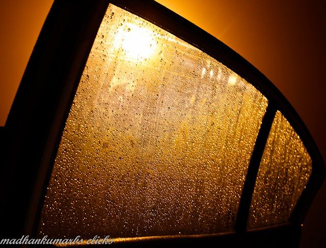 Car window shield in rain, back-lit with street lamp