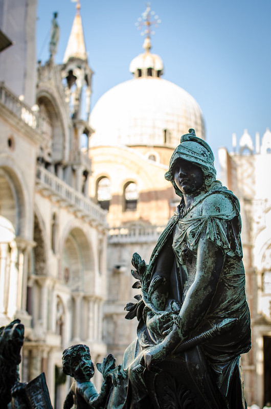 A statue outside the bell tower in St. Mark's Square, the basilica in the background.