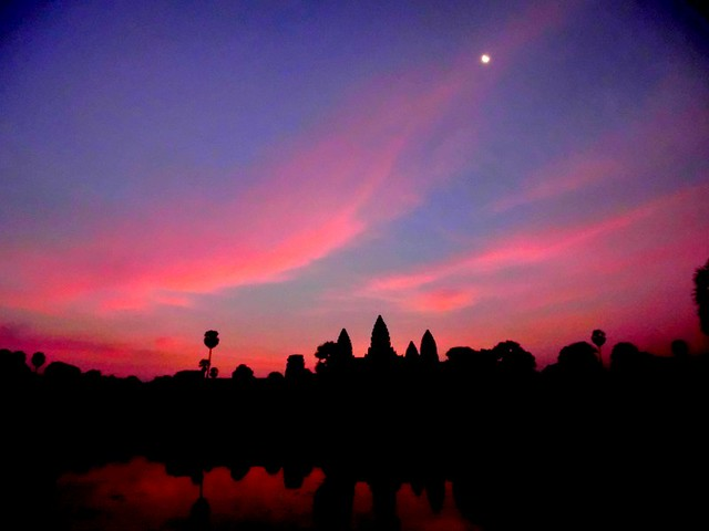 Pink and blue sunrise over Angkor Wat with a half moon overhead