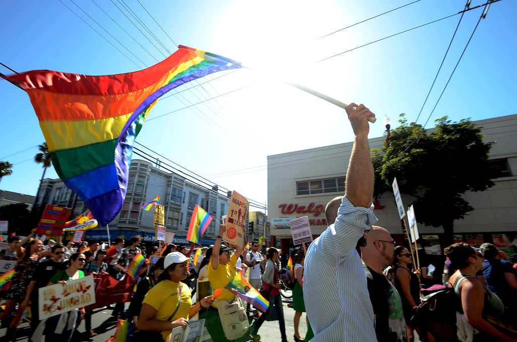 Trey Allen rallies LGBTQ protesters as he waves his flag in front of the Out 4 Immigration Association that is marching down Mission Street for May Day on Wednesday, May 1, 2013. Photo by Frank Leal/Xpress