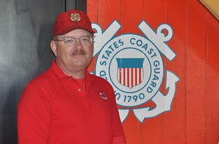 Coast Guard Chief Petty Officer Jesse Meerscheidt poses for a photo in front of a Coast Guard insignia. Meerscheidt pulled a woman from a burning vehicle Oct. 8, 2013, after witnessing a head-on car crash while driving to work. U.S. Coast Guard photograph.