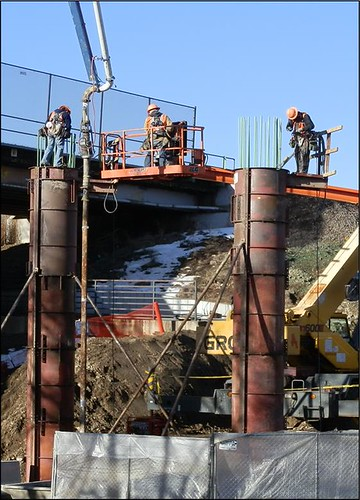 Photo of workers pouring concrete into vertical forms for Clear Creek Bridge support piers