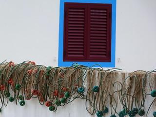 Ventana y redes de pesca en un pueblo de la costa alentejana (Portugal)