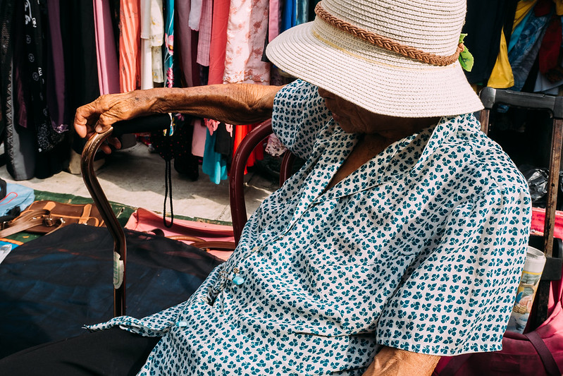 An old lady selling her stuff in a flea market.