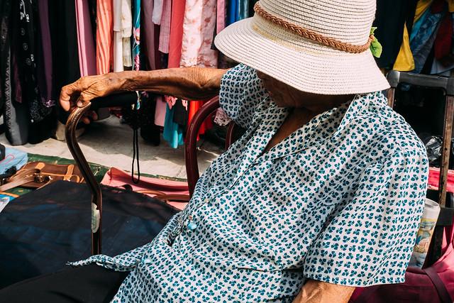 An old lady selling her stuff in a flea market.
