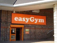 "A close-up view on a double door in a brick wall, with a huge ""easyGym"" sign above in white letters on a bright orange background.  The door frame is in the same orange."