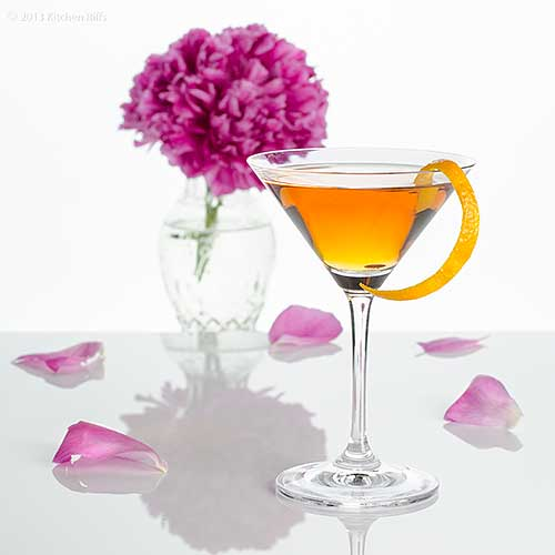 Bridal Cocktail in cocktail glass with orange peel garnish, flowers in background