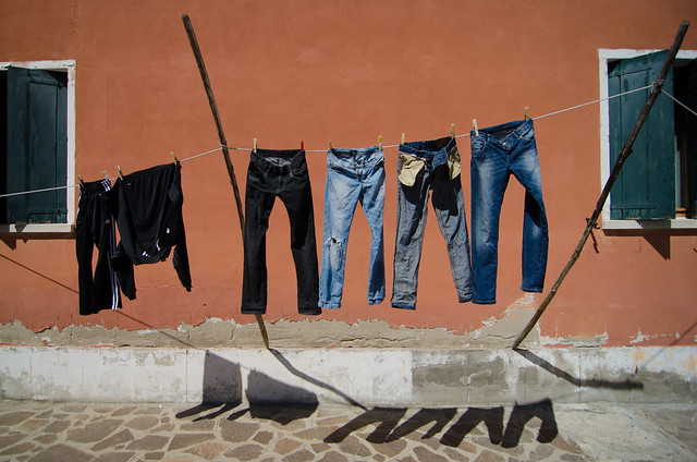Jeans in shadow, colorful laundry on Burano.