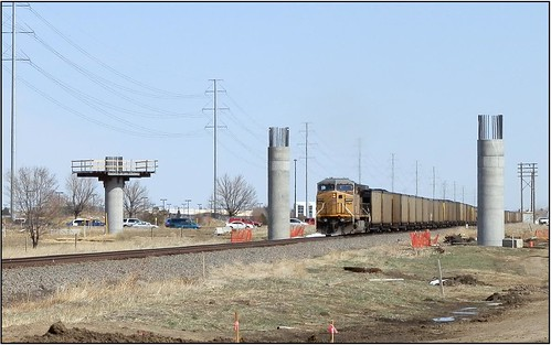 Photo of Union Pacific train headed between support piers for Interstate 70 commuter rail bridge