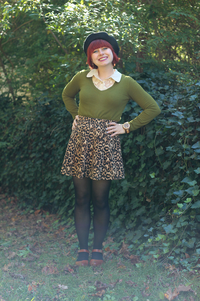 Fall Outfit Featuring an Olive Green Sweater, Leopard Skirt, Wood Watch, Clogs, and a Black Beret