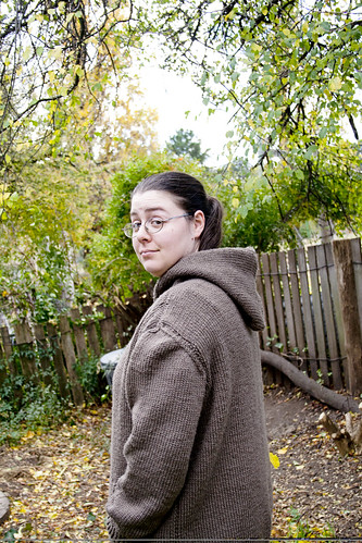 Photo of Ruth wearing a knitted jumper with a hood in a grey/brown colour, taken from the side with the hood down