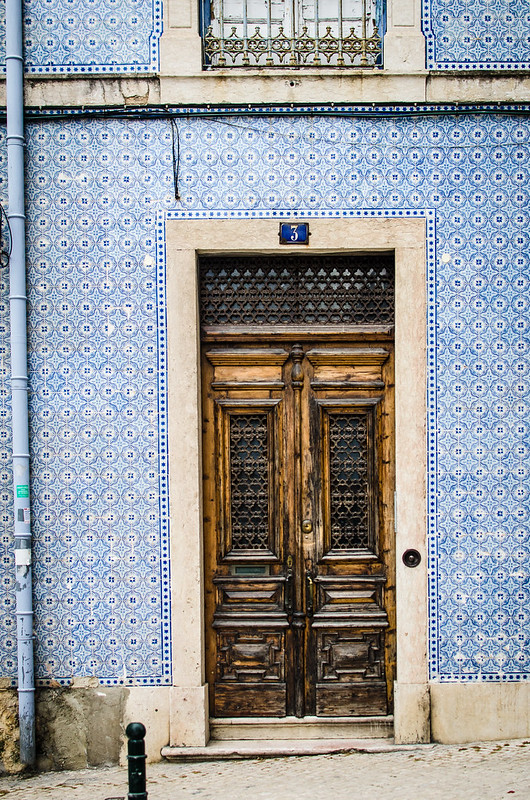 Aged wooden doors surrounded by Lisbon's typical blue Azulejos, or tiles.