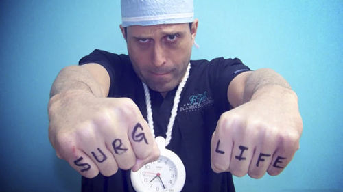 Salzhauer holding his fists out to read SURG LIFE on his knuckles