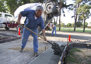 Director Of Facilities Services Scott Maust shovels in some concrete for a new gutter on Berrien Street on Tuesday, July 31.