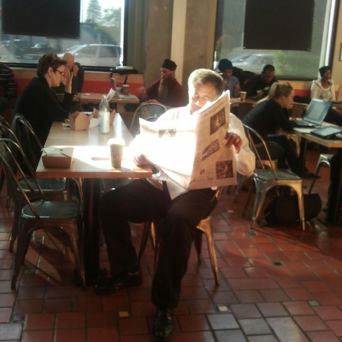 Man reading newspaper at Whole Foods Market in Oakland