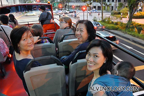 Rachel, Asher, my mum and my aunt smiling for the camera on the bus top