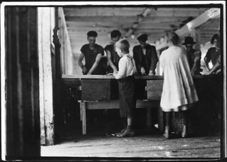 Interior of cutting shed. Young cutters at work, Clarence Goodell 8 years old, and Minnie Thomas, 9 years old. Eastport, Me, August 1911