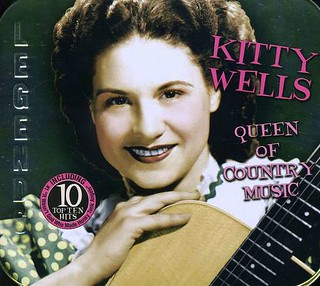 Kitty Wells holding a guitar and looking at the camera