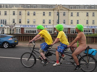 three guys on a tandem with green mankini wearer on back