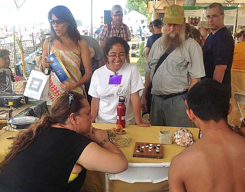 <p>University of Hawaii delegates show visitors how to play a Hawaiian game of strategy at the Smithsonian Folklife Festival.</p>
