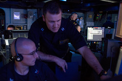 Sailors discuss operations on the Destroyer Squadron 15 watch floor aboard USS Ronald Reagan (CVN 76), Sept. 17. (U.S. Navy/MC3 Sara B. Sexton)