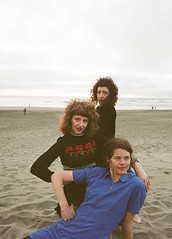 the three members of Grass Widow sitting together on the beach