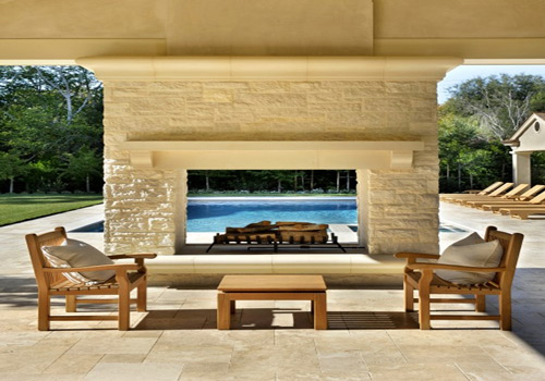 outdoor furniture in front of fireplace and pool