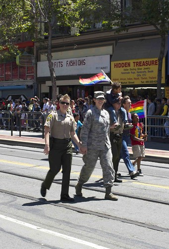 Sheriff's officer walking hand in hand with member of the military