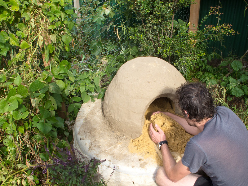 Removing sand from the earth oven