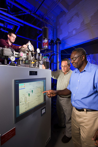 ARS chemical engineer Akwasi Boateng (right) and mechanical engineer Neil Goldberg (center) adjust pyrolysis process conditions while chemist Charles Mullen (left) loads the reactor with bioenergy feedstock.