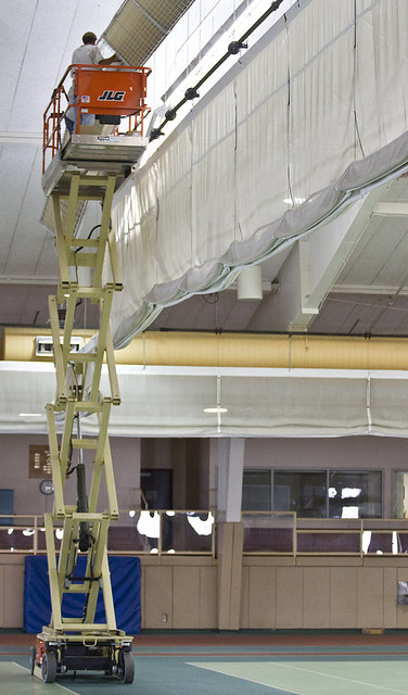 Workers remove old lights in the T. Fleming Fieldhouse on Monday, July 23.