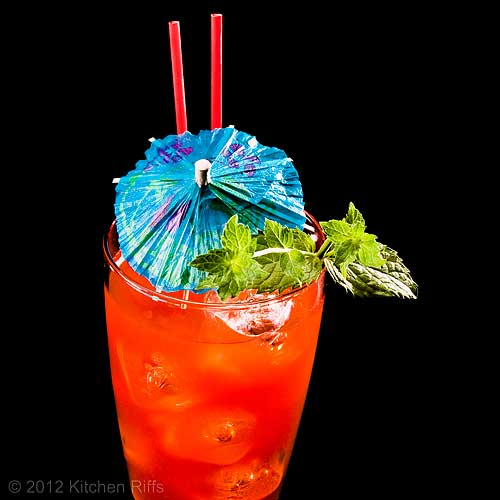 Zombie Cocktail with Mint Sprig and Umbrella Garnish, Black Background