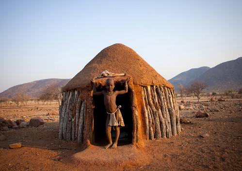 Himba Boy In The Entrance Of His Hut, Okapale, Namibia