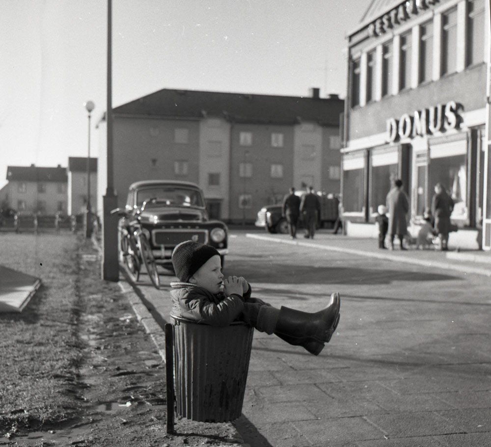 Boy resting in trash can in Gothenburg 1961