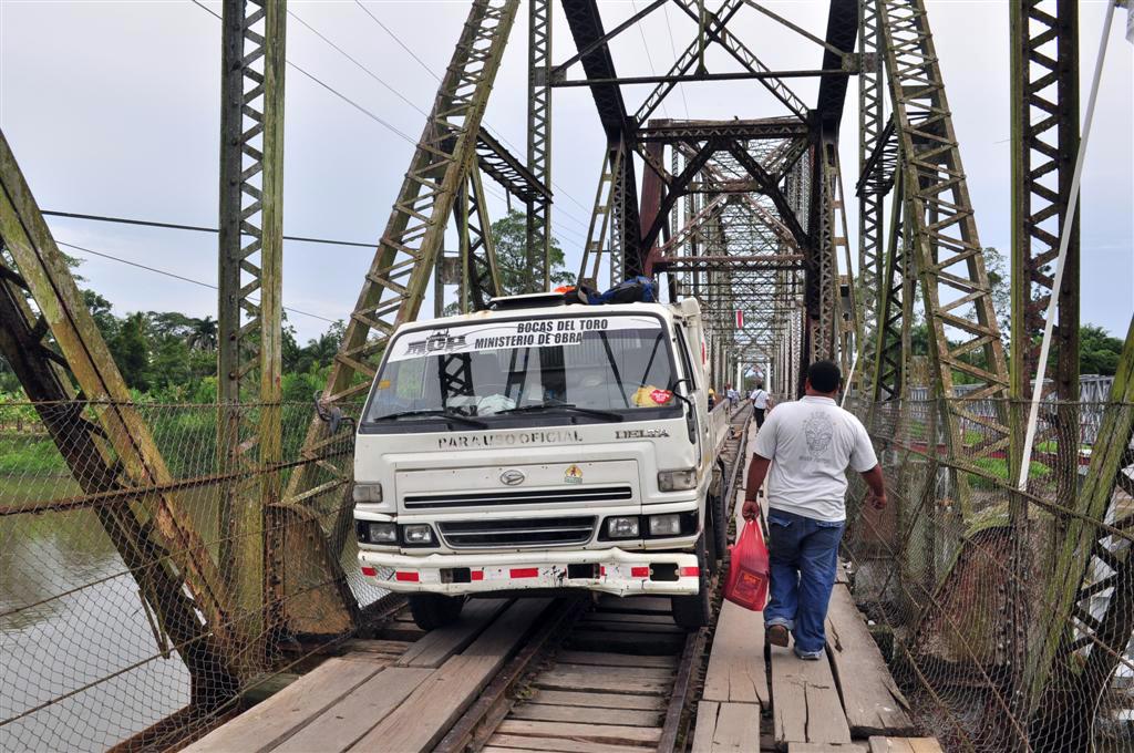 Puente que une Costa Rica con Panamá sobre un Río y por el que circulan personas, caminiones y algún que otro tren, el suelo es de tablones de madera con huecos donde se ve el río. bocas del toro - 7598165400 2a61ccf08a o - Bocas del Toro, escondido destino vírgen en Panamá