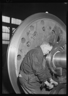 Railroad parts. Baldwin Locomotive Works. Machinist finishing axle on large driving wheels (80 inches in diameter) on newest type of locomotive, March 1937