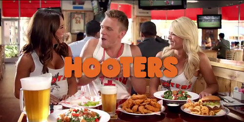 a white guy at a hooters sitting between two waitresses
